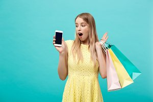 Portrait young attractive woman with shopping bags shows the phone's screen directly to the camera. Isolated on blue background
