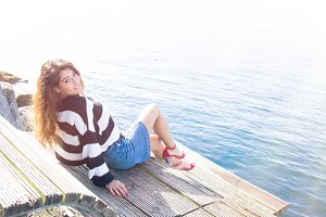 young woman sitting on the pier in f