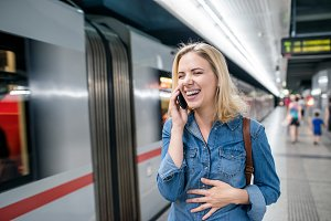 Woman making phone call at the underground platform, waiting