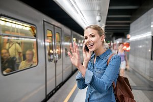 Woman making phone call at the underground platform, waving