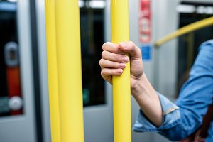 Close up, hand of unrecognizable woman in subway train