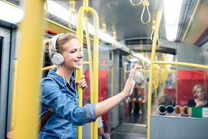 Beautiful young woman with headphones in subway train