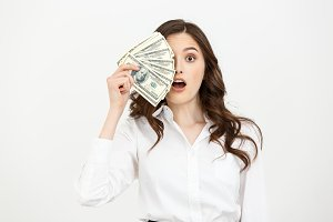 Portrait shocked young business woman standing and holding money isolated over white background.