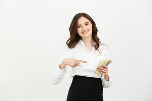Portrait of rich office woman in business wear pointing finger to fan of money isolated over gray background