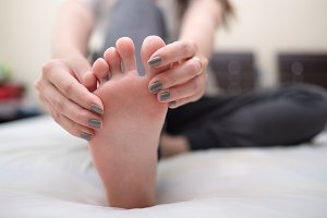 Woman massage foot on bed