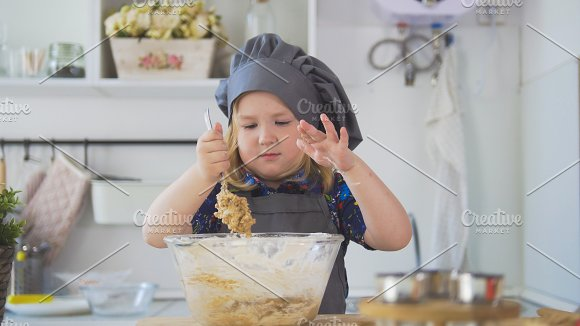 Girl baker mixes the mixture for cookies with a big spoon