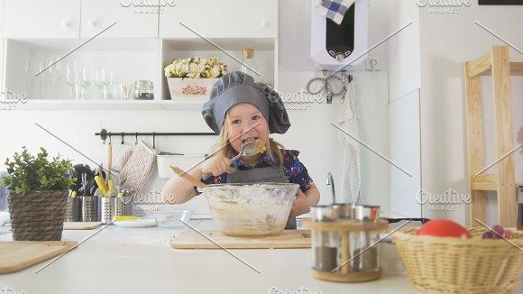 Preschool girl baker mixes the dough in a bowl