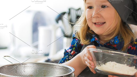 Cheerful little girl make cookies in the kitchen