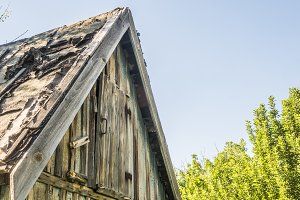 close up old wooden house roof in the countryside against blue sky