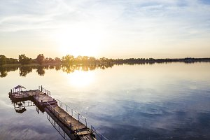 aerial view of pier on a river during fantastic beautiful sunset in countryside