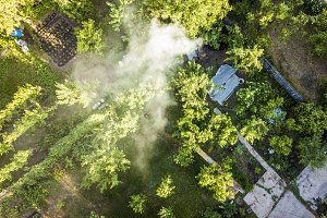 aerial view of smoke from fire between the trees in the garden