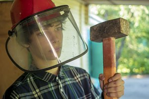 young male worker with sledgehammer in protection mask close up portrait