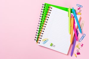 School background with notebooks and colorful supplies