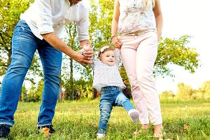 The first steps of the baby. Parents are teaching their child to