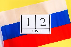 Wooden white calendar with the date of June 12 against the background of the flag of Russia. Russia Day.