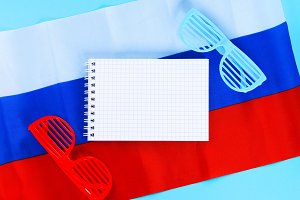 Blank notepad. Red and blue sunglasses. June 12, the Day of Russia. Tricolor of the flag of Russia.