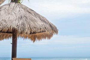 Sun loungers on a white tropical beach near blue ocean shore