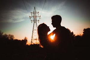 Silhouettes of a guy and girl in a field on a sunset background
