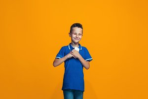 The happy teen boy standing and smiling against orange background.
