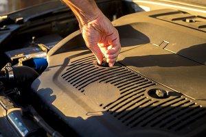 close up hand adjusting car mechanic opening hood during sunset