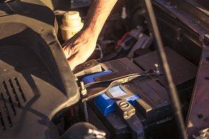 man adjusting car battery in the garage
