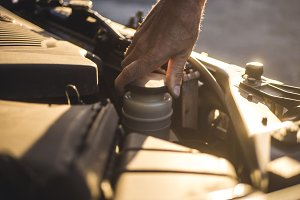 mechanic hand repairing the car with opened hood