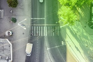 dirctly above view of people walking across the street on a crosswalk