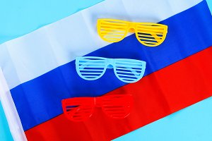 Festive yellow, blue and red glasses. June 12, the Day of Russia. Tricolor of the flag of Russia.