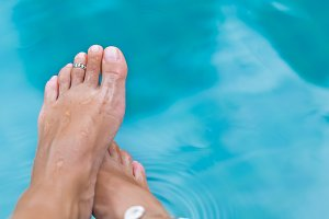 Woman's female legs in blue swimming pool water