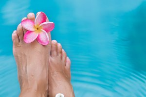 Woman's female legs in blue swimming pool water with frangipani