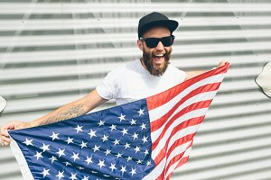 Happy hipster man holding USA Flag