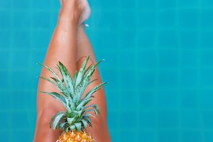 Slim woman holding pineapple fruit near swimming pool tropical e