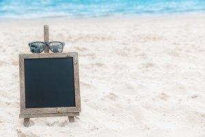 Chalk board with sunglasses on the sea beach sand summer tropic