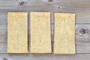Three burlap bags on rustic wood