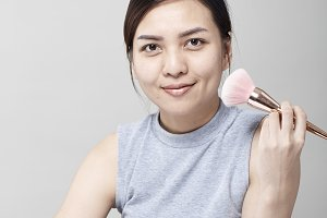 Beautiful young woman applying cosmetic powder on her face with tassel, skin care concept