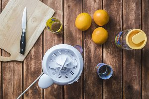 morning preparation of orange juice concept with juicer knife and glasses on a wooden table