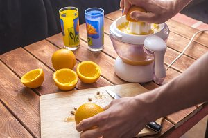 hand squeezing orange fruit to make juice in the morning