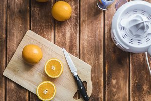 hand cutting fresh oranges with knife on a wooden surface to make juice smoothie