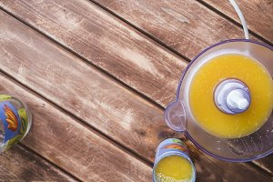 overhead making orange juice smoothie on a wooden table with copy space