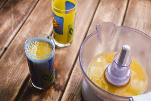 fresh orange juice in the squeezer and glasses on a wooden table