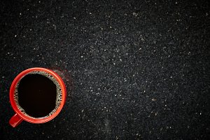 Red cup of black coffee at the morning on table granite background