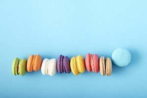 Sweet colorful French macaroon or macaron biscuits on blue