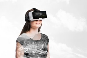Double exposure. Woman with virtual reality goggles. Mountains.