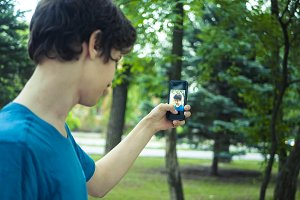 cute teenager boy takes self portrait in the public park with modern phone