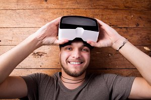 Man wearing virtual reality goggles. Studio shot, wooden backgro