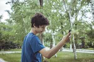 young male teenager boy in t-shir taking selfies with his smartphone