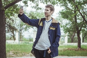handsome young man in casual jacket making selfie with phone walking in the park