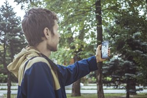 young man in jacket making a selfie outdoors with his smartphone