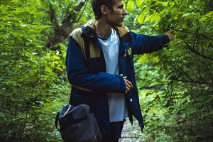 young man walking in dark dense rainforest on the path