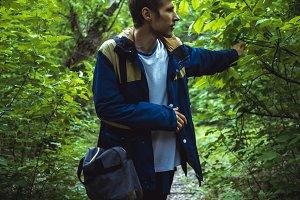 young man walking in dark dense rainforest on the path